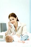 Professional woman using phone in office, smiling at camera, baby lying on desk