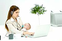 Businesswoman in office, holding sleeping baby, using headset and laptop computer