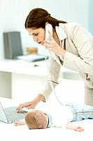Professional woman using phone and laptop computer, baby lying on desk beside her