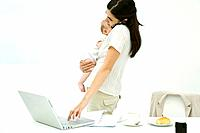 Professional woman standing beside breakfast table, holding baby, using cell phone and laptop computer