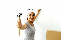 Teen girl showing hammer to the camera, smiling