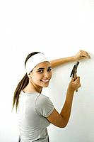 Teen girl hammering nail into wall, smiling over her shoulder at camera