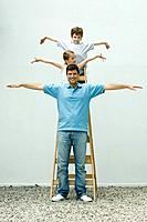Family standing on ladder with arms out, girl looking away, father and son smiling at camera