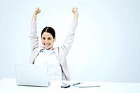 Young businesswoman sitting at desk, smiling at laptop and raising both arms in the air