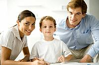 Little boy sitting with parents, drawing with pencil, all smiling at camera