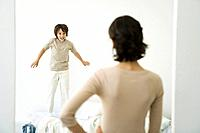 Boy jumping on bed, mother standing in doorway with hand on her hip