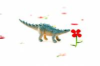 Toy dinosaur smelling artificial flower