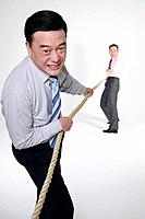 Businessmen playing tug of war