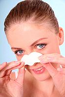 Woman peeling off cleansing strip on her nose