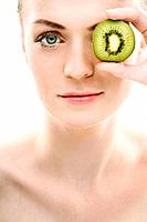 Woman covering her eye with kiwi fruit