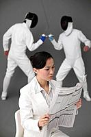 Businesswoman reading newspaper with two men fencing in the background