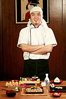 Chef standing in front of served food with his hands folded