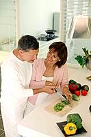 Man guiding woman in cutting vegetable