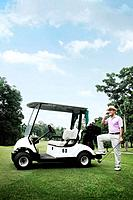Man talking on the mobile phone by the golf cart