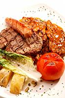 Steak with sausage, boiled potatoes, tomato and lettuce in savoury sauce