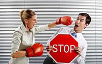 Businessman holding 'Stop' sign, businesswoman punching him