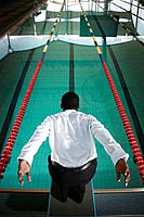 Businessman preparing to dive into the pool
