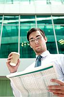 Businessman holding a cup of coffee while reading newspaper (thumbnail)