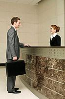 Businessman talking to receptionist (thumbnail)