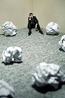 Businessman with giant sized crumpled papers on the floor (thumbnail)