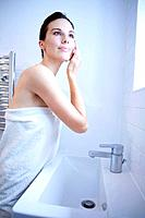 Woman in towel touching her face