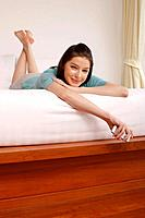 Woman lying forward in bed holding cellphone