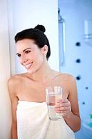 Woman in towel holding a glass of water (thumbnail)