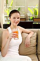 Woman with a glass of fruit juice sitting on the couch (thumbnail)