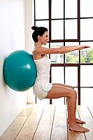 Woman pressing fitness ball against the wall, arms stretching forward