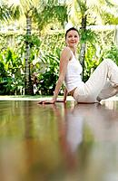 Woman sitting on the floor smiling while looking away (thumbnail)