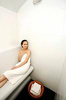 Woman in towel relaxing in the bathroom