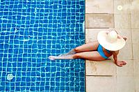 Woman with hat sitting by the poolside