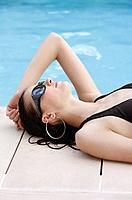Woman with sunglasses relaxing by the poolside