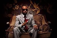 Businessman with sunglasses holding a glass of cocktail