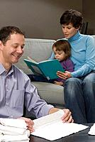 Man folds cloth diapers while woman and child read book on sofa, Winnipeg, Canada