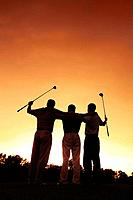 Three men at golf course during sunset