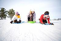 3 kids 14, 13 and 9 years old sliding down hill, Winnipeg, Canada