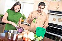 Couple in kitchen cutting vegetables beside kitchen compost bin, Winnipeg, Canada