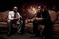 Businessmen sitting on antique sofa talking while having cocktails