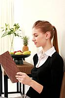 Woman in formal wear reading book