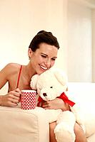Woman hugging a soft toy while holding a mug