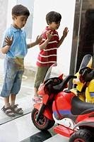 boys looking at toy motorcycles through the shop window
