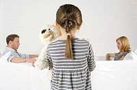 Frustrated couple sitting vis-a-vis, girl holding teddy bear standing in foreground (thumbnail)