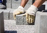 Construction worker setting paving stone
