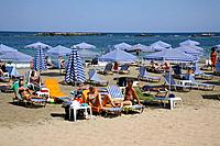 Tourists are sunbathing on a beach on Kreta, Greece