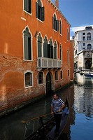 Lone gondolier rowing next to an orange building in Venice