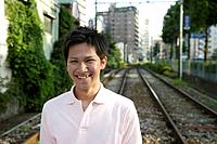 Portrait of a young man smiling on railway track