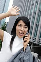 A woman waving hand as she talks on the mobile phone