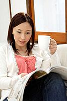 View of a young woman reading a magazine