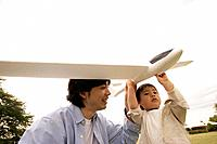 A father helping his son to hold an aeroplane